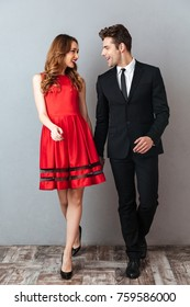 Full length portrait of a happy smiling couple dressed in formal wear walking while holding hands and looking at each other over gray wall background