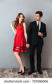 Full length portrait of a happy smiling couple dressed in formal wear posing while holding hands and looking at each other over gray wall background