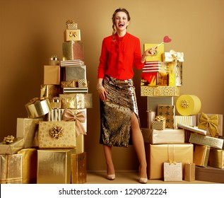 Full length portrait of happy stylish fashion-monger in red blouse and golden sparkly sequin pencil skirt with red heart shaped candy among 2 piles of golden gifts in front of a plain wall.