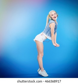 Full length portrait of a happy stylish woman posing over blue background