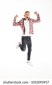 Full length portrait of happy teenage boy wearing casual clothing screaming in delight and clenching fists on camera like winner or smart pupil isolated over white background