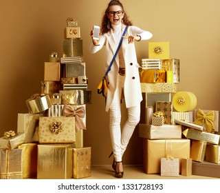Full length portrait of happy trendy shopper woman in white clothes among 2 piles of golden gifts in front of a plain wall paining at smartphone blank screen. Shop smarter online with smartphone.