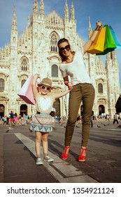 Full length portrait of happy trendy mother and daughter with colorful shopping bags in the front of Cathedral in Milan, Italy.
