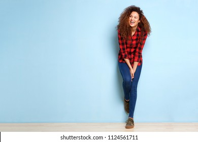 Full length portrait of happy woman leaning against blue background
