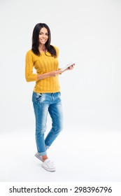 Full Length Portrait Of A Happy Woman Standing And Holding Tablet Computer Isolated On A White