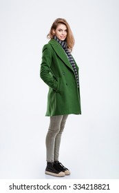 Full length portrait of a happy woman in coat standing isolated on a white background and looking at camera