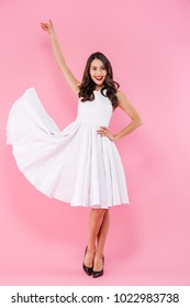Full length portrait of a happy young asian woman dressed in white dress posing while standing isolated over pink background
