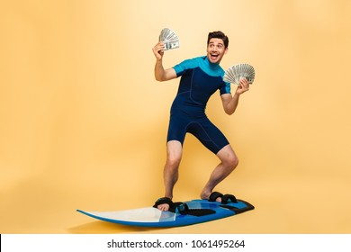 Full length portrait of a happy young man dressed in swimsuit holding bunch of money banknotes while surfing on a board isolated over yellow background