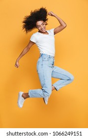 Full length portrait of a happy young african woman celebrating success while jumping isolated over yellow background
