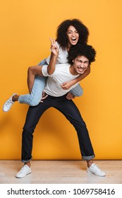 Full length portrait of a happy young african guy giving piggyback ride to girlfriend isolated over yellow background