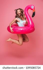 Full length portrait of a happy young woman dressed in swimsuit jumping with inflatable flamingo isolated over pink background