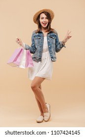 Full length portrait of a happy young girl in summer clothes holding shopping bags isolated over beige background