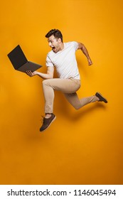 Full length portrait of a happy young man jumping with laptop computer isolated over yellow background