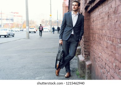 Full length portrait of a happy young formal dressed man leaning on a wall outdoors