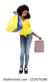 Full length portrait of happy young black woman with shopping bags standing against isolated white background