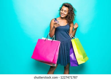 Full length portrait of a happy young woman holding shopping bags and mobile phone isolated on a green background