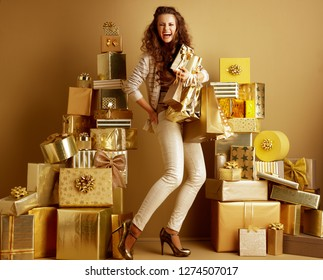 Full length portrait of happy young fashion-monger in gold beige clothes among 2 piles of golden gifts in front of a plain wall holding present boxes and shopping bags. holidays shopping illustration.