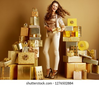 Full length portrait of happy young woman in gold beige clothes among 2 piles of golden gifts in front of a plain wall showing present box. first minute shopping with huge gift opportunities concept
