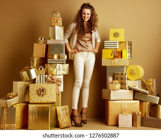 Full length portrait of happy young fashion-monger in gold beige clothes standing among 2 piles of golden gifts in front of a plain wall. first minute shopping with huge gift opportunities concept.