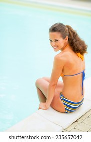 Full length portrait of happy young woman sitting at poolside