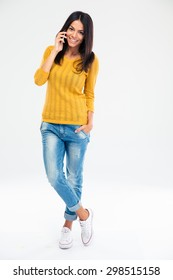 Full length portrait of a happy young woman talking on the phone isolated on a white background