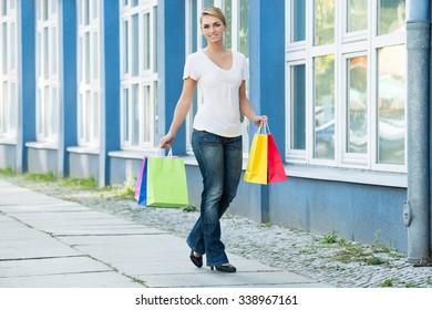 Full length portrait of happy young woman carrying shopping bags on sidewalk