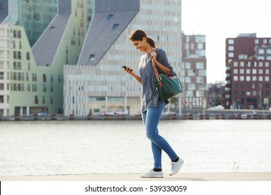 Full length portrait of happy young woman walking water in city with mobile phone