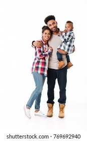 Full length portrait of a happy young african family with their little son standing together isolated over white background