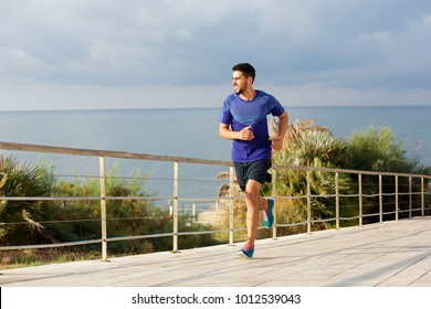 Full length portrait of healthy young man running outside with earphones