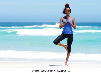Full length portrait of healthy young woman doing yoga balance exercise at the beach