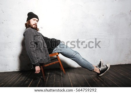 Full length portrait of a hipster man in hat sitting on chair isolated over wall background