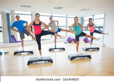 Full length portrait of instructor with fitness class performing step aerobics exercise in gym