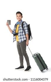 Full length portrait of joyful Asian tourist with suitcase and passport posing for photography against white background
