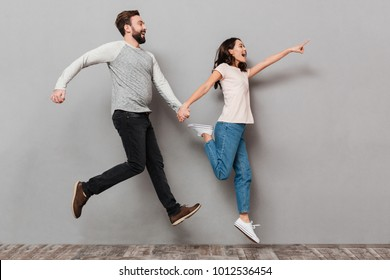 Full length portrait of a joyful young couple jumping together and pointing away over gray background