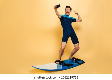 Full length portrait of a joyful young man dressed in swimsuit taking a selfie while surfing on a board isolated over yellow background