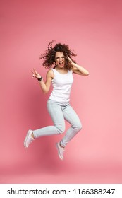 Full length portrait of a joyful young woman jumping and celebrating over pink background