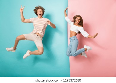 Full length portrait of a joyful young couple jumping over two colored background