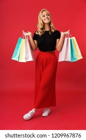 Full length portrait of joyous blond woman 20s smiling and holding colorful shopping bags isolated over red background in studio