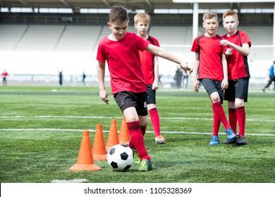Full length portrait of junior football team practicing in stadium, focus on teenage boy leading ball between  row of orange cones, copy space