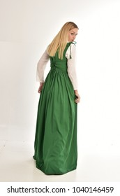 full length portrait of lady wearing green fantasy, medieval outfit. standing pose wit back to the camera, on white studio background.
