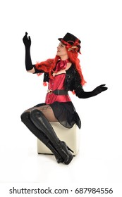 full length portrait of lady wearing cabaret inspired costume, seated pose. isolated against white background.