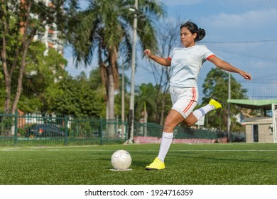 Full length portrait of a latin female soccer player about to kick the ball. Female football player concept
