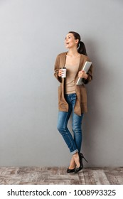Full length portrait of a laughing young asian woman holding cup of coffee and laptop computer while standing and looking away at copy space over gray background