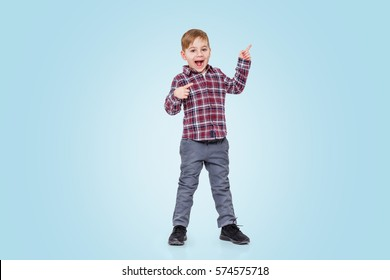 Full length portrait of a little boy standing and pointing finger away isolated over blue background