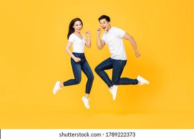 Ganzes Portrait von hübschem asiatischem Paar, das in der Mitte der Luft einzeln auf gelbem Hintergrund lächelt und springt