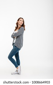 Full length portrait of a lovely casual girl standing and looking away isolated over white background