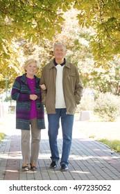 Full length portrait of lovely senior couple strolling through the park arm in arm.