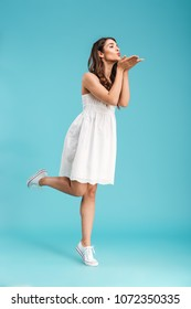 Full length portrait of a lovely young girl in summer dress sending kiss while standing isolated over blue background