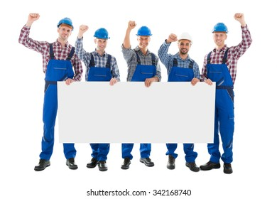 Full length portrait of male carpenters with arms raised holding blank billboard over white background