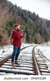 Full length portrait of a male hiker standing with arms folded on railway